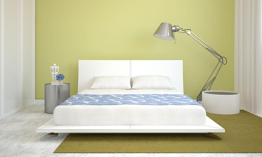un lit king size dans une cambre aux murs vert et blanc