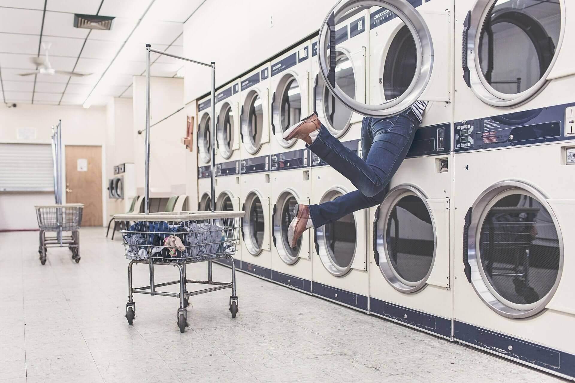 homme mettant la tête dans un lave linge