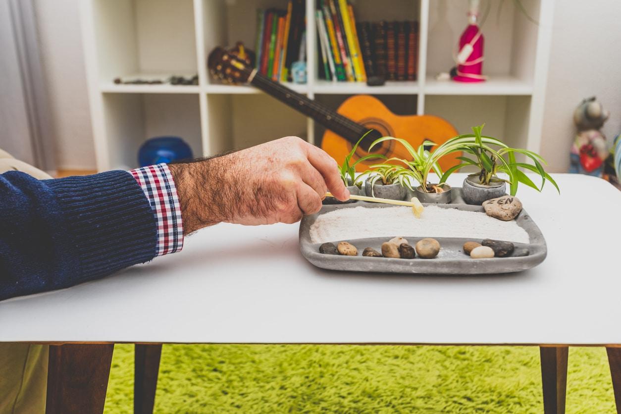 Homme utilisant son jardin zen miniature
