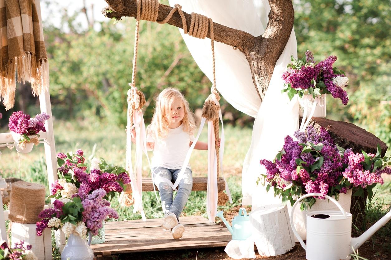 Petite fille sur balancelle dans un jardin