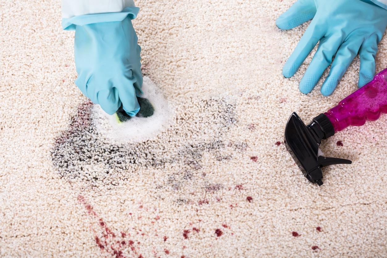 Tache de tapis avec une éponge de nettoyage